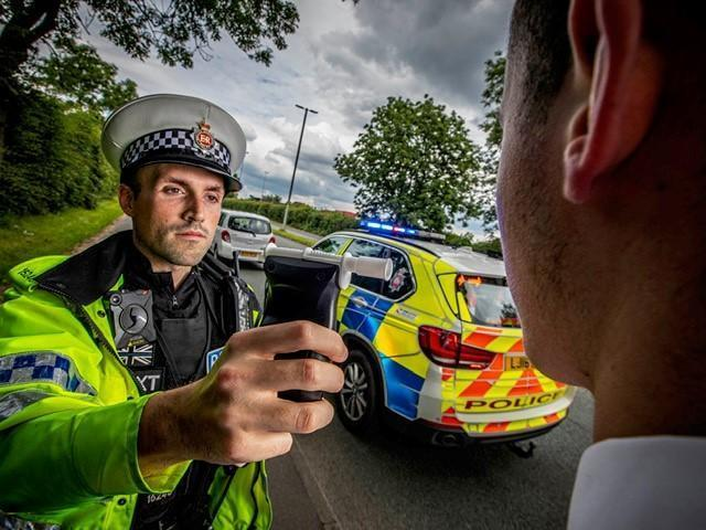 A driver is breathalysed at the roadside