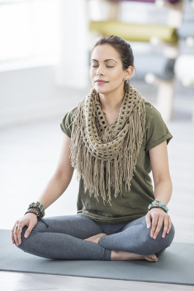 A Caucasian woman is indoors in a fitness studio. She is wearing casual exercise clothing and a scarf. She is sitting cross-legged on a yoga mat and meditating with her eyes closed..