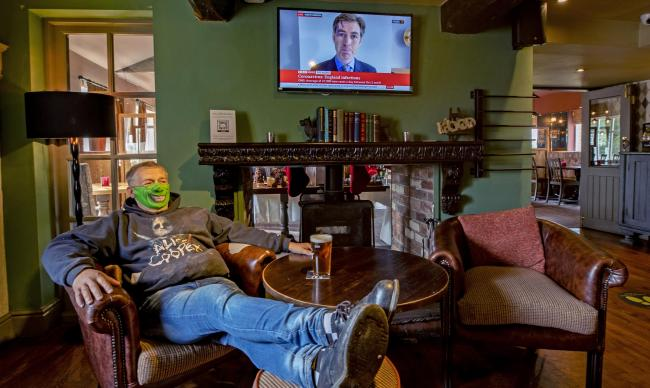 A customer enjoys a drink whilst watching a news broadcast about lockdown restrictions at the Bull and Dog public house in Burscough, Lancashire.  (Peter Byrne/PA)