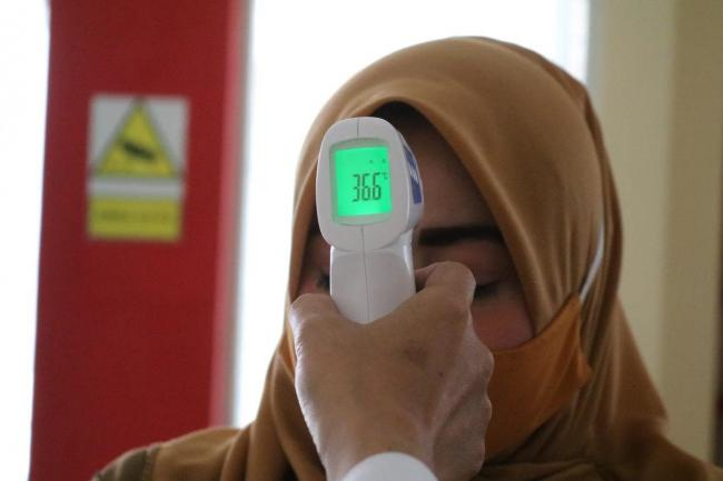 A woman has her temperature read via a temperature scan of her forehead