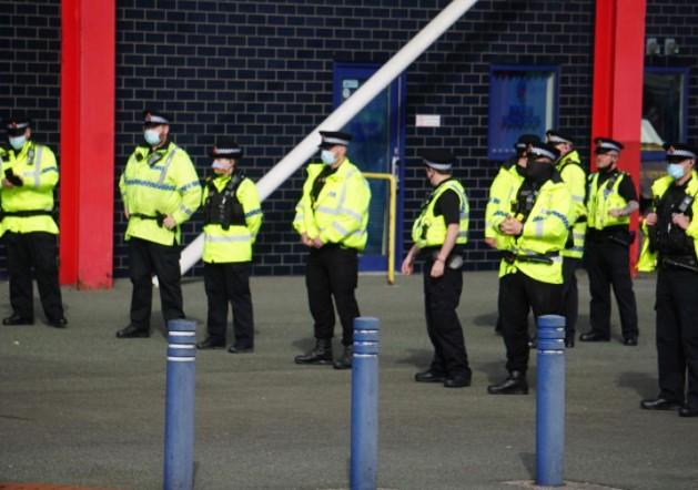 Police line up after Saturday's game to clear trouble at the University of Bolton Stadium