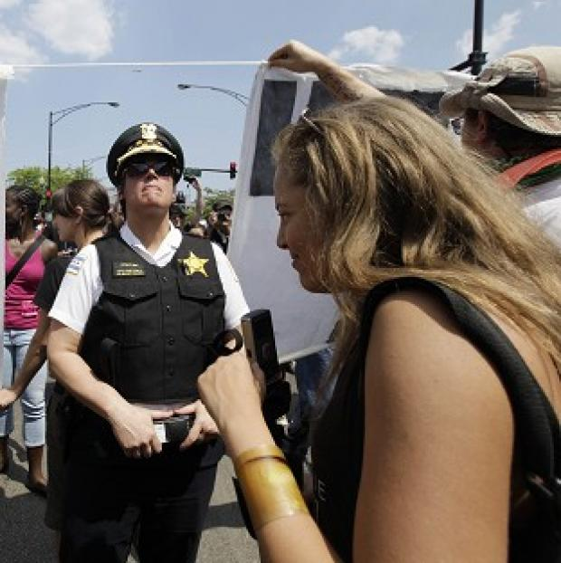 A Chicago police officer monitors the area during a march on Montrose Avenue during a Nato summit demonstration in Chicago (AP Photo)