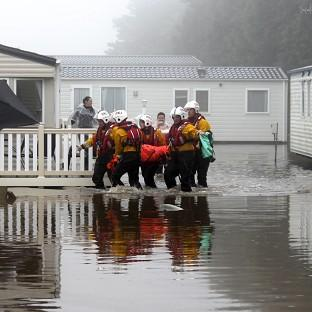 Volunteers from Filey RNLI lifeboat station and the coastguard rescue people from their caravans in Cayton Bay in North Yorkshire