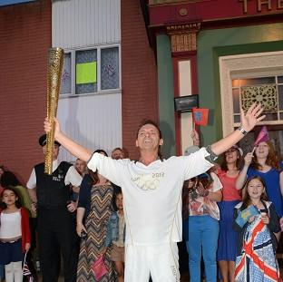 Perry Fenwick carrying the Olympic flame during an episode of EastEnders (Kieron McCarron/BBC/PA)