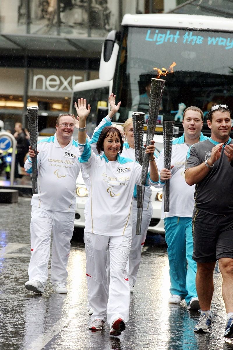 The torchbearing team, including Serena Blackburn (number 089), carry the Paralympic Flame on the Torch Relay leg between The City of London and Tower Hamlets