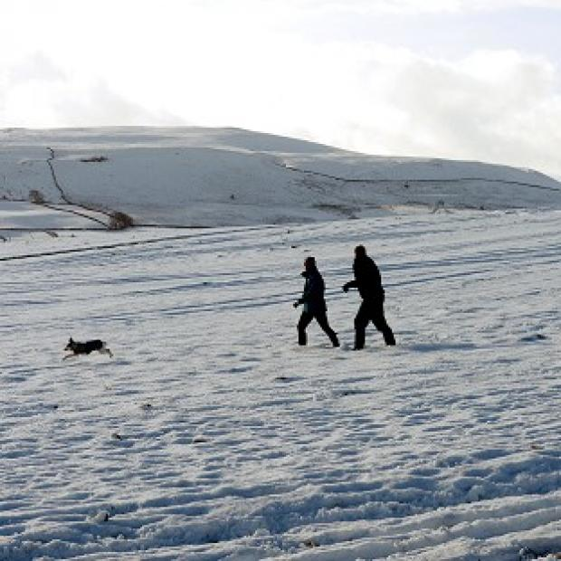 This Is Lancashire: Walkers in the snow as they cross Middleham Moor in The Pennines