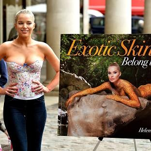 Helen Flanagan poses beside a PETA poster featuring her wearing reptile skin