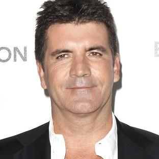 Simon Cowell is enjoying working with the new panel of judges on The X Factor USA