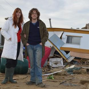 This Is Lancashire: Wesley Woods and Helen Robinson with their caravan in Walcott, Norfolk, which was wrecked by the tidal surge last week