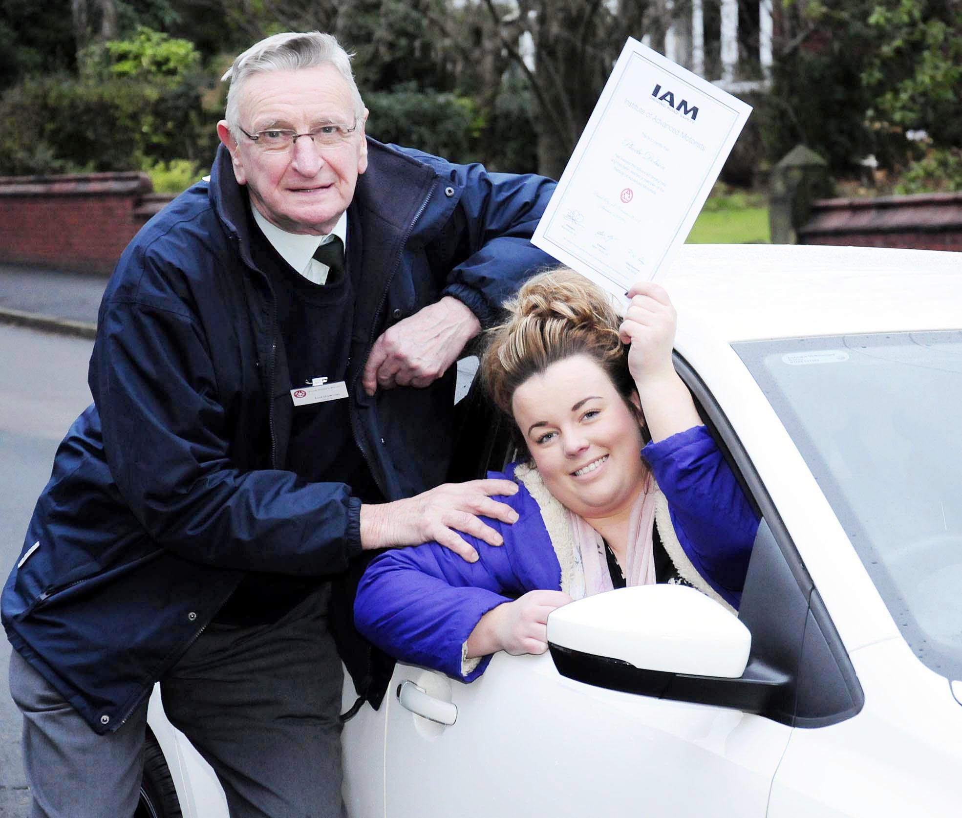 Phoebe Dobson waves her Advanced Motorist pass certificate congratulated by her grandad, Ted Rowson