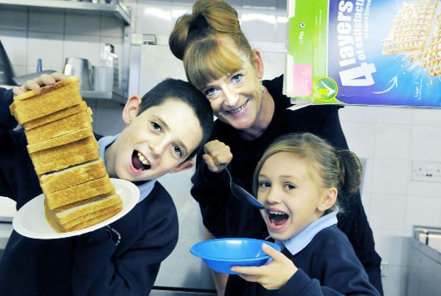 Pupils Liam Mason, aged 11, and Chelsea Jones, aged 9, enjoy the Breakfast Club at Our Lady's Primary School, Blackburn, with supervisor Lisa Mason