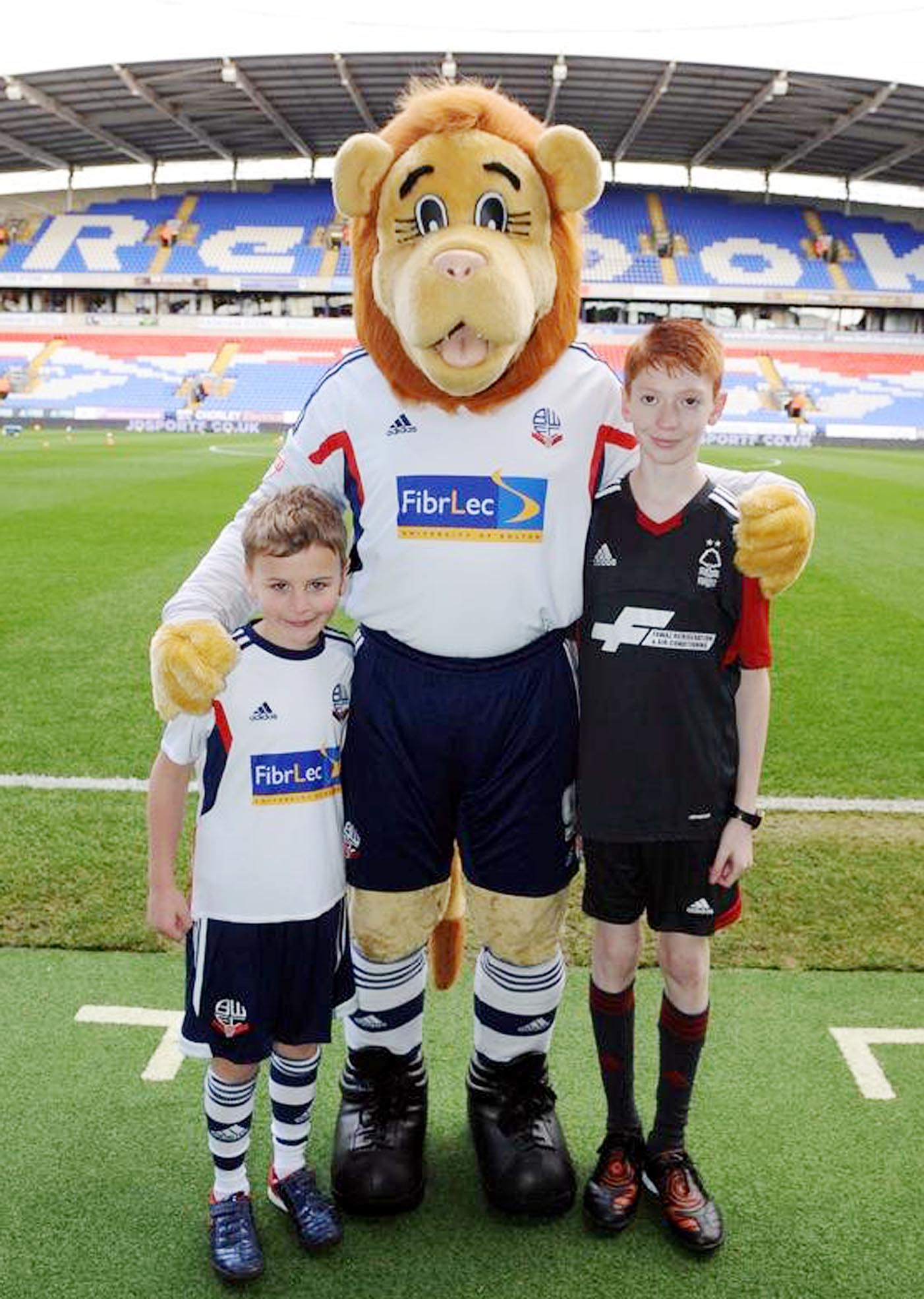 Young fan leads out Bolton Wanderers after winning competition at shopping centre