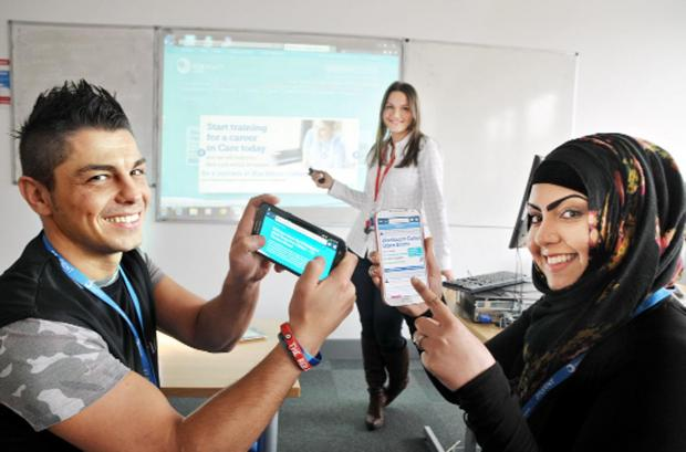 Lecturer Joanne Fardella, centre, shows students Russell Bury and Halima Sharif how gadgets can be used in the classroom
