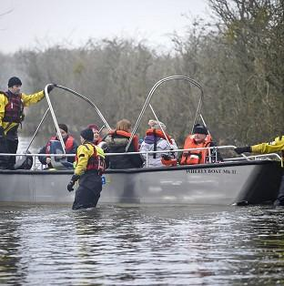 This Is Lancashire: Stranded residents onboard a rescue boat as they are transported from the village of Muchelney in Somerset, after it was cut off by flooding