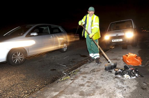 This Is Lancashire: A worker cleans up after the crash on the A6 in Blackrod