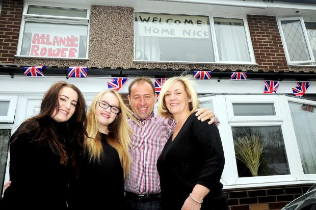 This Is Lancashire: Nick Griffiths beneath the bunting with daughters Amy and Hannah and wife Janine