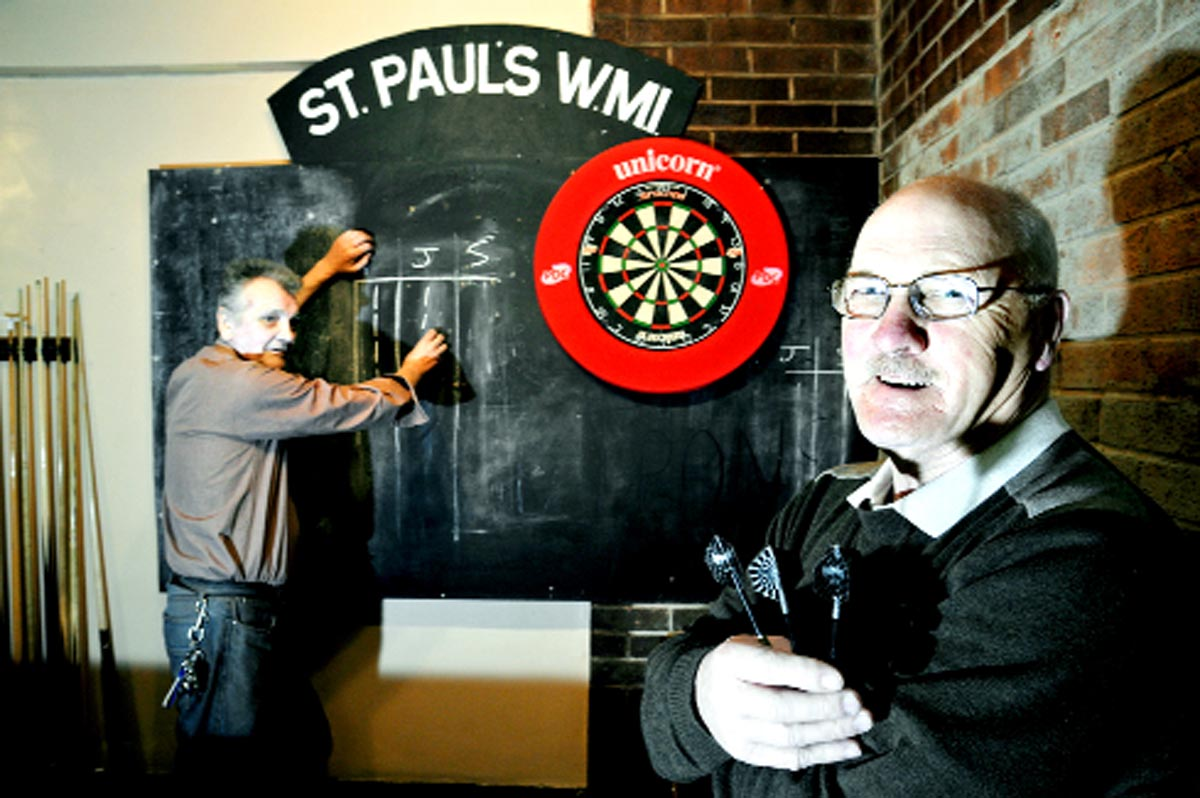 Tom Kellie, left, and Joe Carlin play darts.