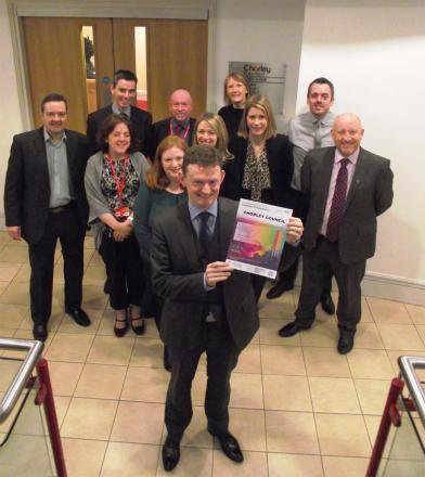 HONOURED: Cllr Peter Wilson, centre, celebrates achieving the Workplace Wellbeing Charter with council staff