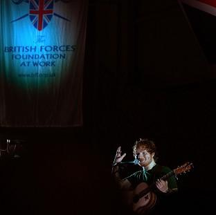 This Is Lancashire: Ed Sheeran performing to British troops at Camp Bastion at the weekend, where he played two gigs supported by comedian Craig Campbell, he met troops going about their duties in Britain's desert base.