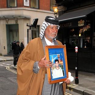 This Is Lancashire: Mizal Karim Al-Sweady, the father of Hamid Al-Sweady carries a photo of his son after leaving the inquiry into his death.
