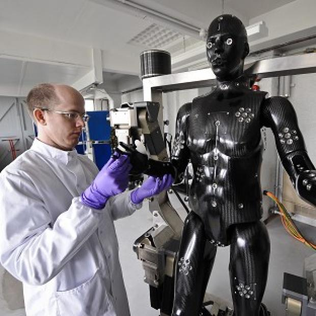 This Is Lancashire: Jaime Cummins checks the Porton Man robot mannequin that will help test the next generation of chemical and biological suits for the UK's armed forces