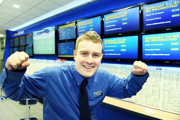 This Is Lancashire: Peter Fuller, customer service advisor at William Hill in Burnley, with the odds on the Clarets gaining promotion.
