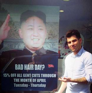 This Is Lancashire: Barber Karim Nabbach standing next to a poster poking fun at North Korean leader Kim Jong-un unusual hairstyle, as North Korean officials visited the salon over the display of their leader's poster in the salon's window.