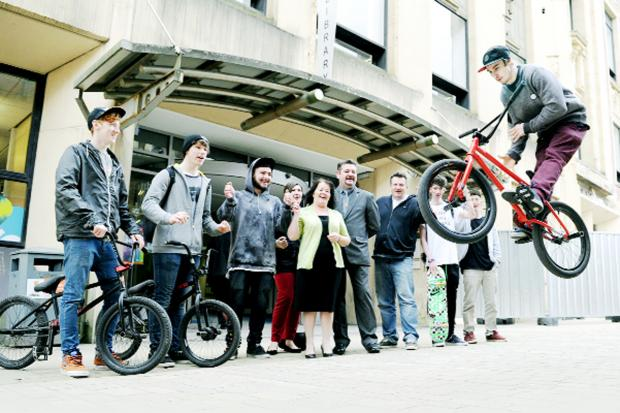 This Is Lancashire: Mike Curley shows off his bike tricks watched by Coun Kate Hollern, Coun Trevor Maxfield, skaters and bikers