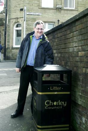 Coun Adrian Lowe next to one of the new-style bins outside Chorley Town Hall