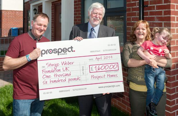 Paul Callaghan, left, receives the cheque from John Pearson of Prospect Homes watched by Matilda and Rebecca Callaghan