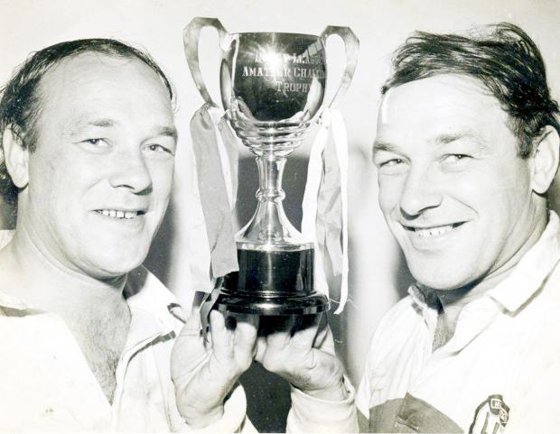 Robert Dowling, left, lifts another trophy for Leigh Miners with his twin brother Paul