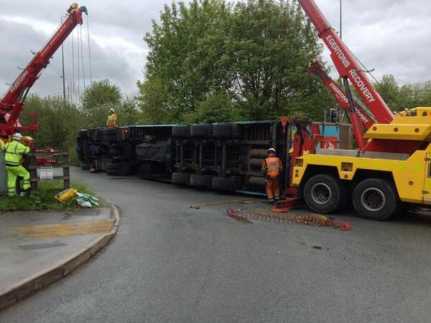 This Is Lancashire: Emergency service workers removed the lorry after it fell on its side