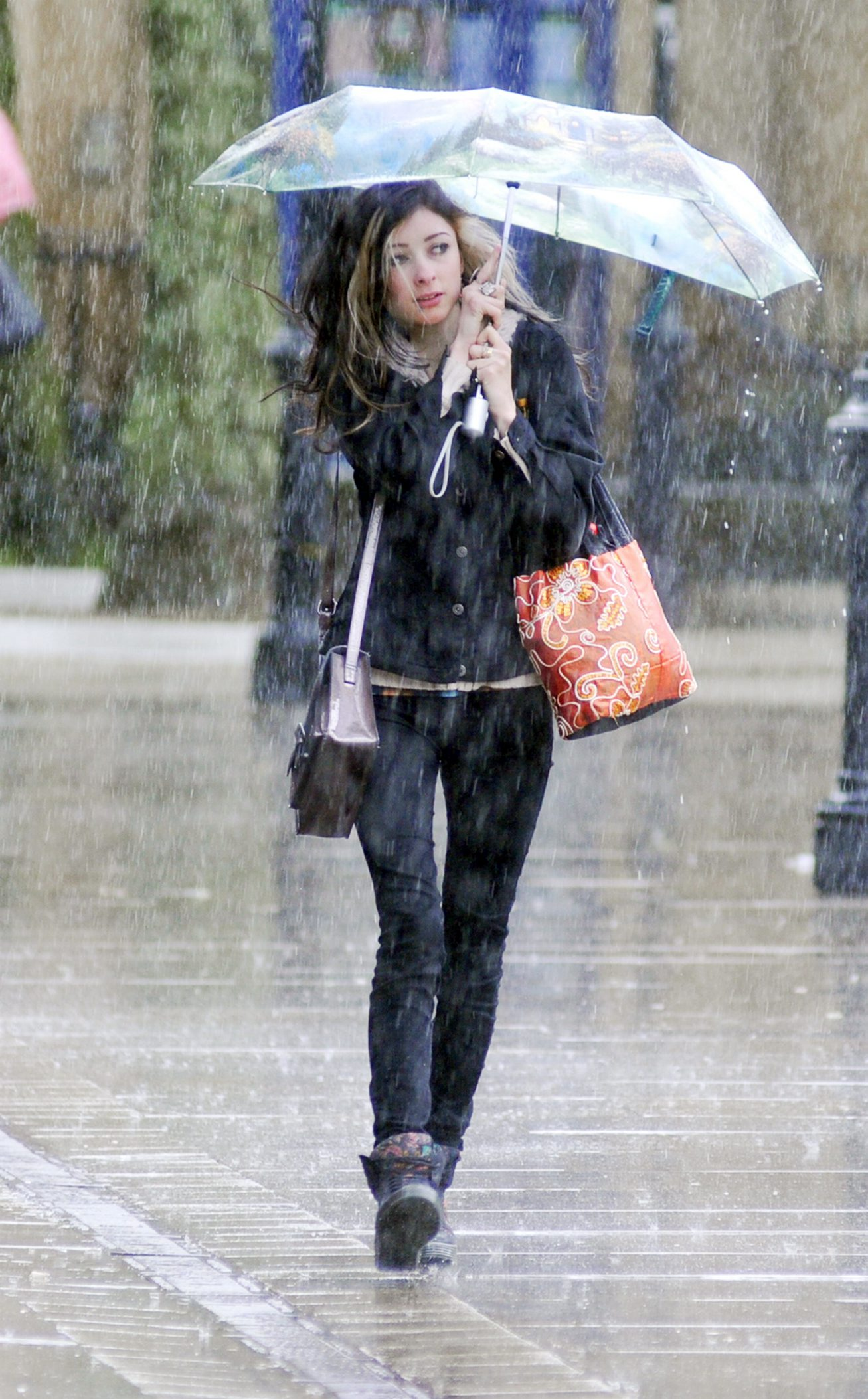 A shopper braves the wind and rain in Bolton town centre