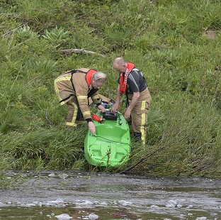 Rescue services retrieve a kayak at Riding Mill Pumping station on the River Tyne in Northumberland where three kayakers died