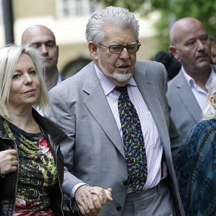 This Is Lancashire: Rolf Harris arrives with his family at Southwark Crown Court in London (AP)