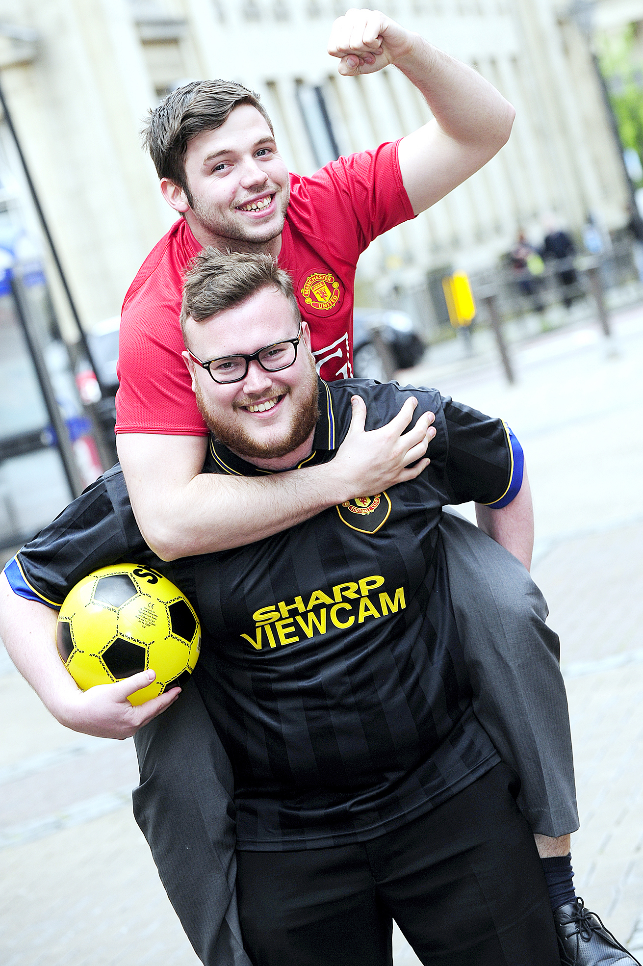 Liam Thorp gets a piggyback from Andrew Bardsley for their trip to the Manchester United ground