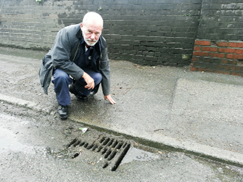 Coun Paul Browne examined one of the blocked drains