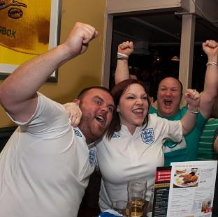 This Is Lancashire: England fans cheer their team in the pub