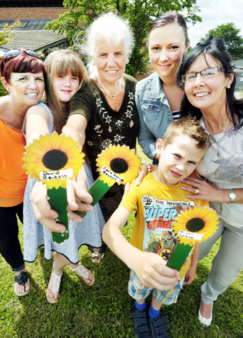 From left, Gail Balderson, Amelia Whitehead the great granddaughter of Mary Beckett, centre, who lost her husband David, Gemma Swallow with her son Alfie, front, and Alexandra Skene who lost her husband Allan, Alfie's grandfather  – with their wooden