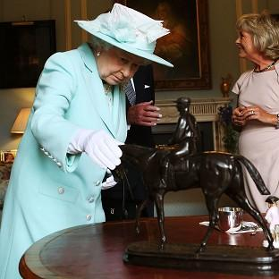 The Queen inspects a piece by French sculptor Pierre-Jules Mene during the filming of Antiques Roadshow