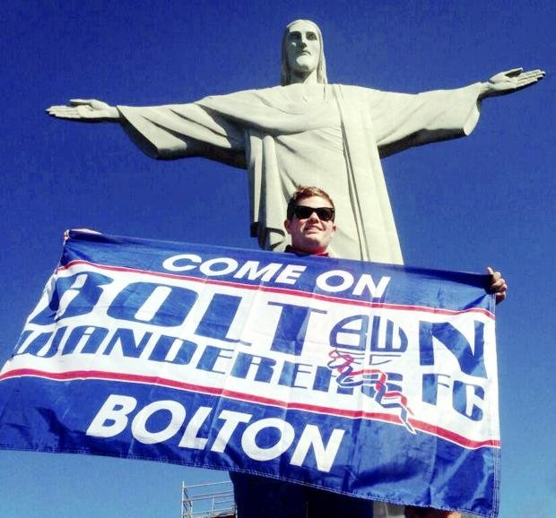 Whites supporter Joel Hughes proudly displaying the Bolton Wanderers flag in front of the iconic Christ the Redeemer statue in Rio de Janeiro