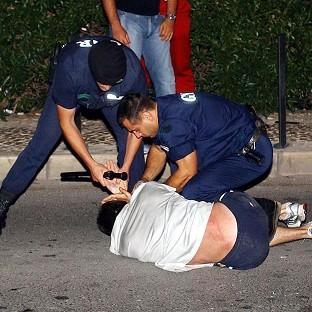 Portuguese police restrain a fan during disturbances at Albufeira on the Algarve during Euro 2004
