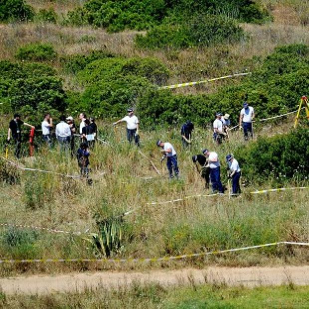 This Is Lancashire: British police and their Portuguese counterparts search a patch of scrubland on the Algarve