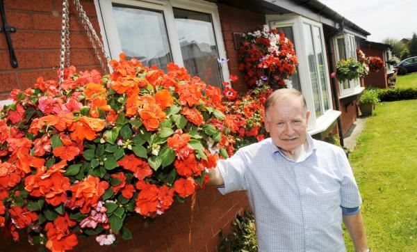 This Is Lancashire: Mr Lowry with his remaining hanging baskets