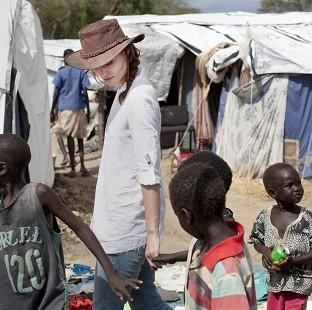This Is Lancashire: Keira Knightley holds hands with displaced children in Bor Camp, South Sudan