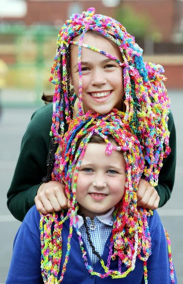 This Is Lancashire: Ruby Jones, front, aged seven, and Lois Mawhinney, aged 10, go loom band crazy at an after-school club in Smithills, where youngsters have produced a 300-metre-long giant bracelet.