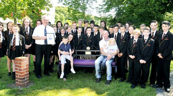 This Is Lancashire: Head Teacher Bob Wakefield and students present the Memorial Bench for Robbie Williamson at Shuttleworth College. Seated on the bench are Robbie's family. From left, Coby Hewitt, Nicola Grimshaw, Dean Williamson and