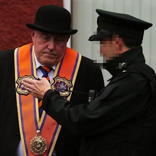 This Is Lancashire: Senior Orange man Spencer Beattie speaks to a police officer on Woodvale Road in Belfast