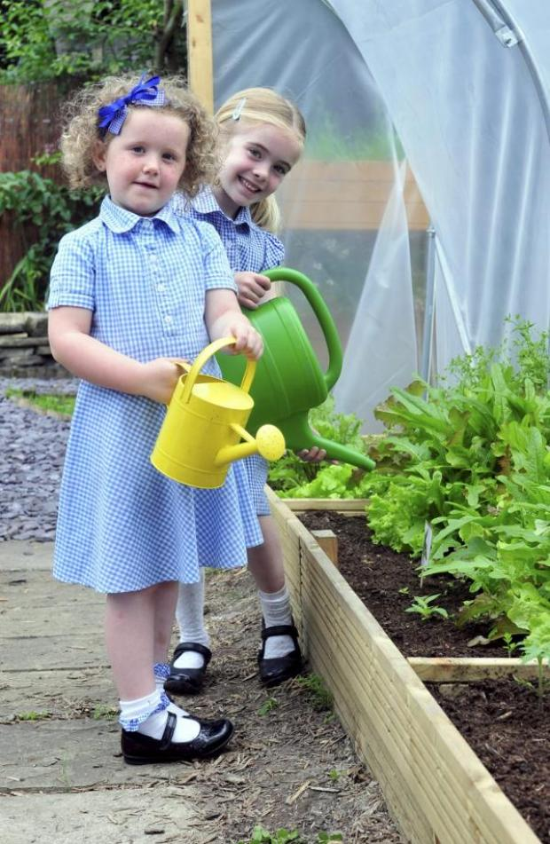 This Is Lancashire: Watering in the greenhouse are,  Evie Dickens and Erin Palmer