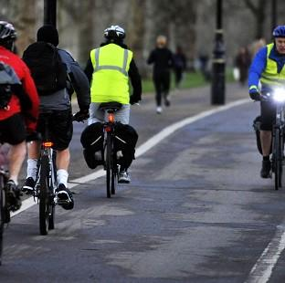 Commuters make their way on bicycles through London's Hyde Park
